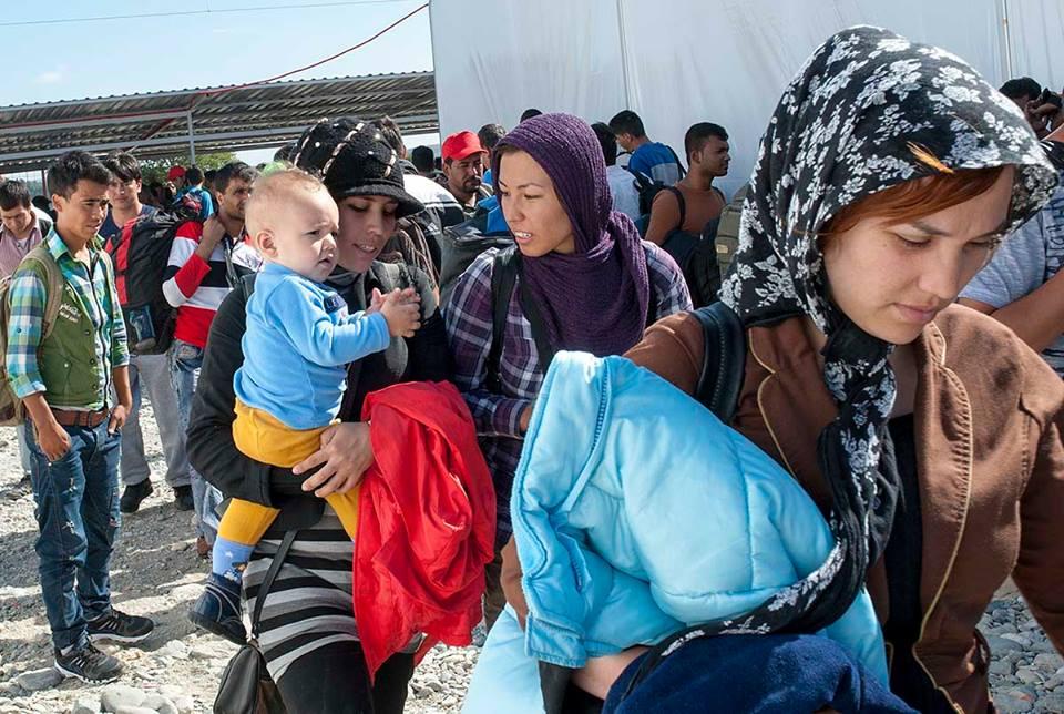 Хуманитарните работници вадат купишта облека од која бегалците внимателно бираат што им треба и пикаат во торби / Фото: Роберт Атанасовски