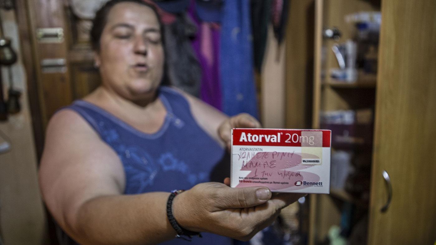 Василики Кацула држи една од многуте кутии лекови што ги дели со своите родители во нивниот дом во Атина. Фото: Ана Пантелиа