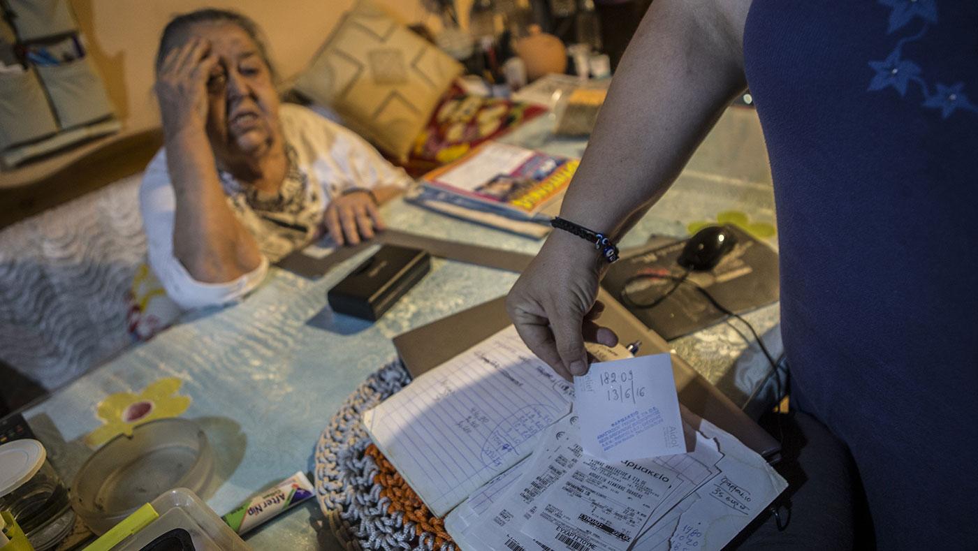 Василики Кацула, на фотографијата со нејзината мајка Елени, држи медицински сметки во нивниот дом во атинската област Аспропиргос. Фото: Ана Пантелиа
